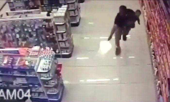 This screen capture from a pharmacy security video shows Sgt. Souza chasing a remaining robber after having shot the other, gun in one hand, infant in the other. (Screen shot, International Business Daily)