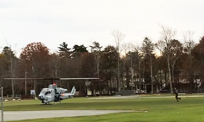 A Marine Corps crewman runs back to the helicopter with the missing cellphone. (Mount Desert islander/YouTube)