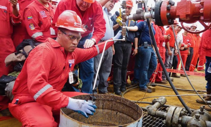 A technician takes a sample of crude oil from a well operated by Venezuela's state-owned oil company PDVSA in Morichal, Venezuela. (Ramon Sahmkow/AFP/Getty Images)