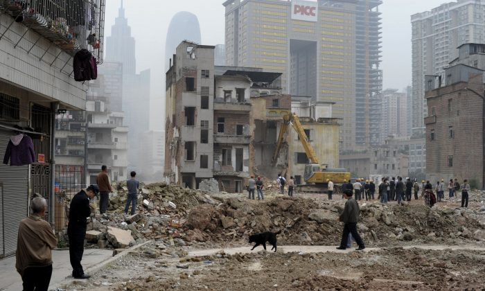 Workers demolish a group of villagers' houses in Yangji village, Guangzhou City in southern China, on March 21, 2012. A recent corruption case revealed how officials can easily profit off such housing demolitions. (STR/AFP/Getty Images)