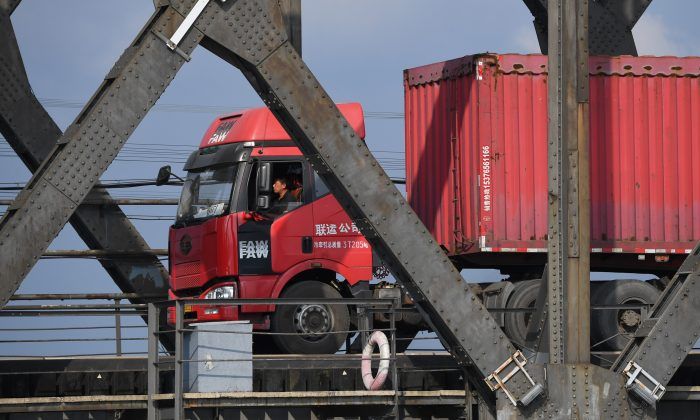 A truck returns over the Friendship Bridge, from the North Korean town of Sinuiju to the Chinese border city of Dandong, in China's northeast Liaoning province on Sept. 5, 2017. The Broken Bridge once connected Dandong and the North Korean town of Sinuiju, but was bombed by the US during the Korean war and now only reaches half way across the Yalu River. (GREG BAKER/AFP/Getty Images)