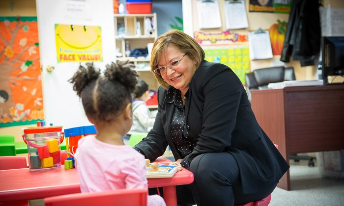 Carla Tellez, founder of Our Children First, a therapeutic learning center for children, is with a child at the center in the Bronx borough of New York on Nov. 22, 2017. (Benjamin Chasteen/The Epoch Times)