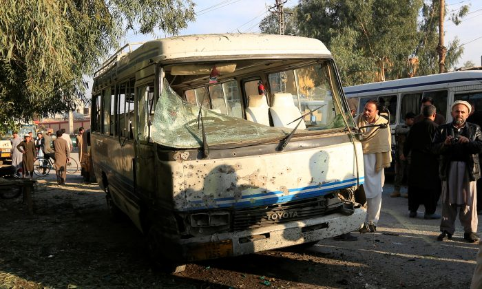 People look at a damaged bus after a suicide attack in Jalalabad city, Afghanistan November 23, 2017. In a separate incident, ISIS terrorists in the region beheaded 15 of their own (Reuters/Parwiz)