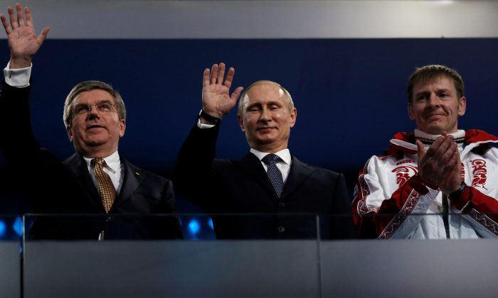 International Olympic Committee (IOC) President Thomas Bach of Germany and Russian President Vladimir Putin wave as gold medallist bobsleigh athlete Russia's Alexander Zubkov applauds (L-R) during the closing ceremony for the 2014 Sochi Winter Olympics, on Feb. 23, 2014.        (REUTERS/Phil Noble/File Photo)