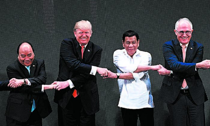 (L–R) Vietnamese Prime Minister Nguyen Xuan Phuc, President Donald Trump, Philippine President Rodrigo Duterte, and Australian Prime Minister Malcolm Turnbull link hands during the opening ceremony of the 31st ASEAN Summit in Manila, Philippines, on Nov. 13. (NOEL CELIS/AFP/GETTY IMAGES)