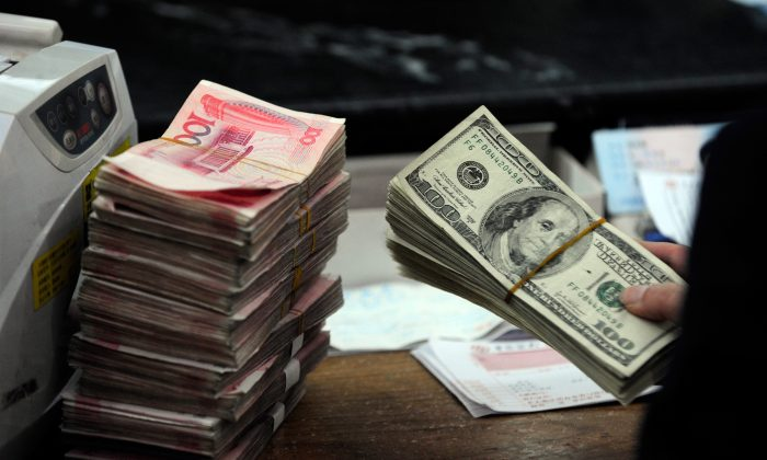 A stack of U.S. dollars together with stacks of 100 Chinese yuan notes at a bank in Hefei City in eastern China's Anhui Province on March 9, 2010. (STR/AFP/Getty Images)