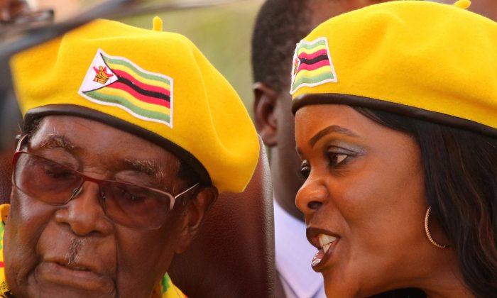 President Robert Mugabe listens to his wife Grace Mugabe at a rally of his ruling ZANU(PF) party in Harare, Zimbabwe, November 8, 2017.  (Reuters/Philimon Bulawayo/File Photo)