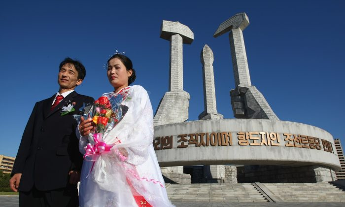 A North Korean couple celebrates their wedding at a monument to North Korea's ruling Worker's Party on Oct. 19, 2007, in Pyongyang, North Korea.  Wedding celebrations face possible trouble after a new decree banned drinking alcohol in groups larger than three in North Korea. (Alexander Hassenstein/Getty Images)