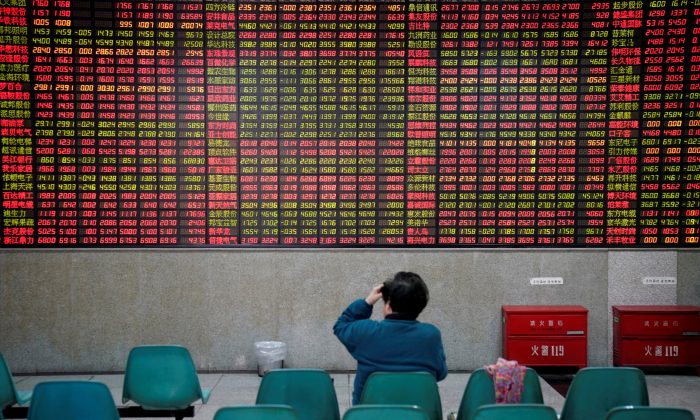 An investor watches board showing stock information at a brokerage house in Shanghai on Nov. 24, 2017. (REUTERS/Aly Song