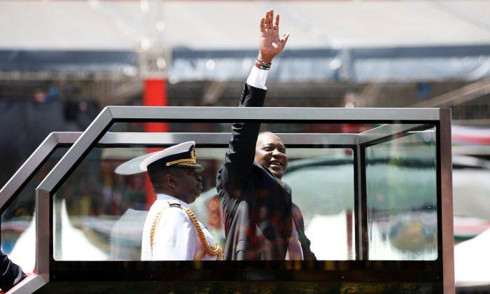 Kenya's President Uhuru Kenyatta waves upon his arrival to his inauguration ceremony where he will be sworn in as president at Kasarani Stadium in Nairobi, Kenya, Nov. 28, 2017. (Reuters/Baz Ratner)