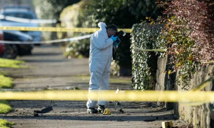 A crime scene investigator photographs the site of a car crash in which five people, including three children, were killed after a stolen car crashed into a tree on Stonegate Road, in Leeds, northern England on Nov. 25, 2017.  (Oli Scarff/AFP/Getty Images)