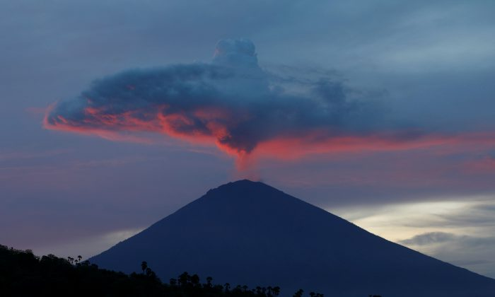 A plume of smoke above Mount Agung volcano is illuminated at sunset as seen from Amed, Karangasem Regency, Bali, Indonesia, November 30, 2017. (Reuters/Darren Whiteside)
