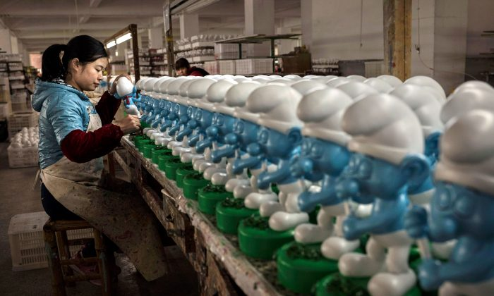 "A Chinese worker paints unfinished licensed ceramic ""Smurfs"" at a factory in Dehua County, Fujian Province, China on December 7, 2014. (Kevin Frayer/Getty Images)"