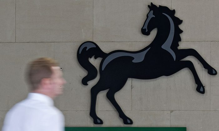 A man passes a Lloyds logo outside the entrance to an office of Lloyds Banking Group in the City of London on July 28, 2016. (Justin Tallis/AFP/Getty Images)