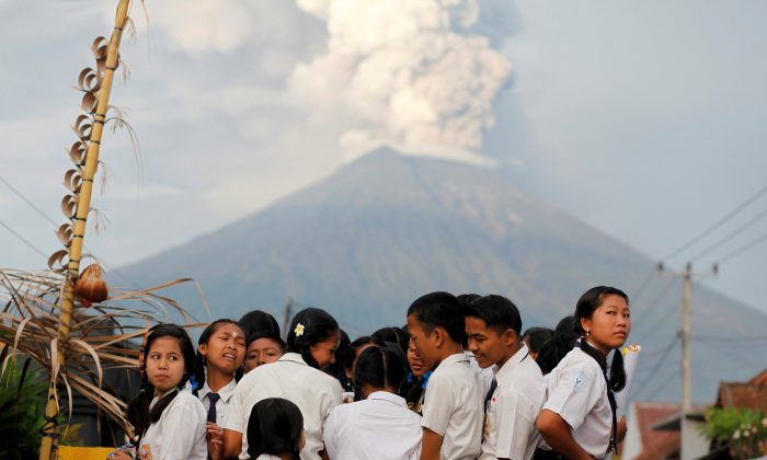 School children ride on the back of a truck on their way to school as Mount Agung volcano erupts in the background near Amed, Karangasem Regency, Bali, Indonesia. (Reuters/Nyimas Laula)