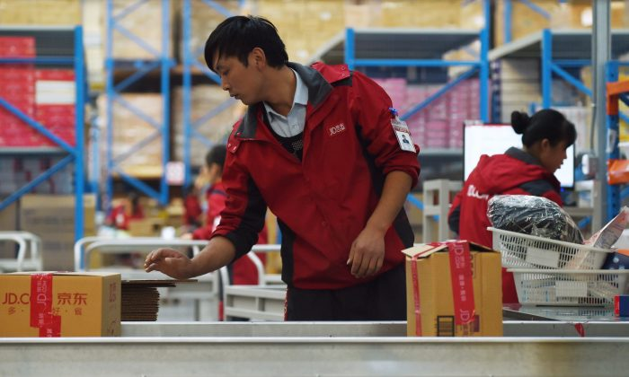 A JD.com employee checks goods from a conveyor belt at a warehouse in Langfang, China's Heibei province, on Nov. 3, 2015. (WANG ZHAO/AFP/Getty Images)