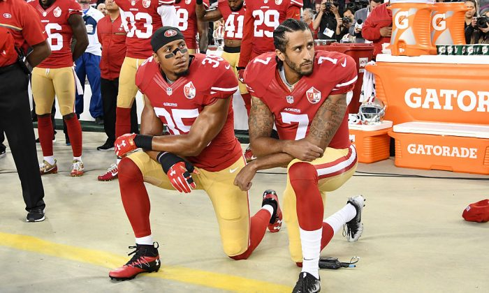 Colin Kaepernick and Eric Reid kneel in protest during the National Anthem on Sept. 12, 2016. (Photo by Thearon W. Henderson/Getty Images)