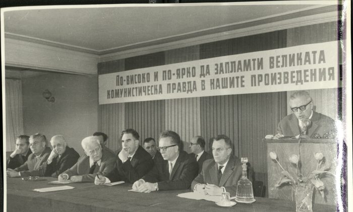 """Dimitar Dimov speaks at a meeting of the Association of Bulgarian Writers in 1964. Among those sitting are Panteley Zarev (second row, second left), Georgi Karaslavov (first row, fifth from left) and Kamen Kalchev (first row, seventh from left), who were some of the most fervent critics of the novel """"Tyutyun."""" The slogan above them reads: """"Let the great Communist idea spark ever higher and stronger in our literary works."""" (National Museum of Bulgarian Literature)"""