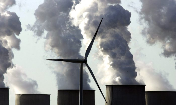 A loan wind turbine spins as exhaust plumes from cooling towers at a coal-fired power station in Jaenschwalde, Germany, on April 12, 2007. (Sean Gallup/Getty Images)