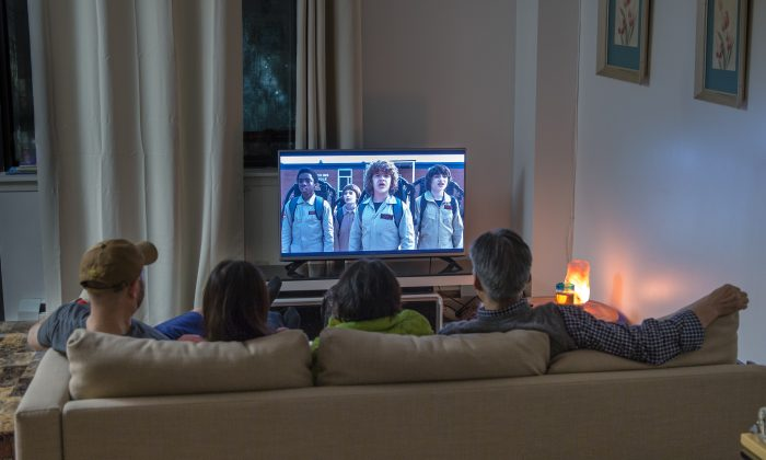 """A family streams the Netflix show """"Stranger Things"""" at their home in Queens, New York, on Dec. 6, 2017. (Benjamin Chasteen/The Epoch Times)"""