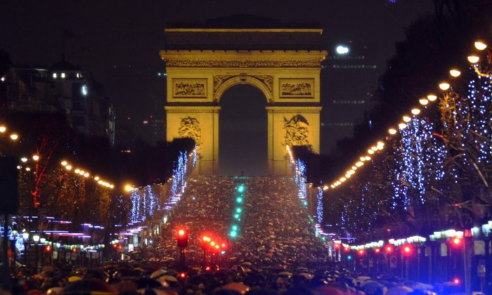 People gather on the Champs-Elysees avenue in Paris to celebrate the New Year, late on December 31, 2012. AFP PHOTO / MIGUEL MEDINA        (Photo credit should read MIGUEL MEDINA/AFP/Getty Images)