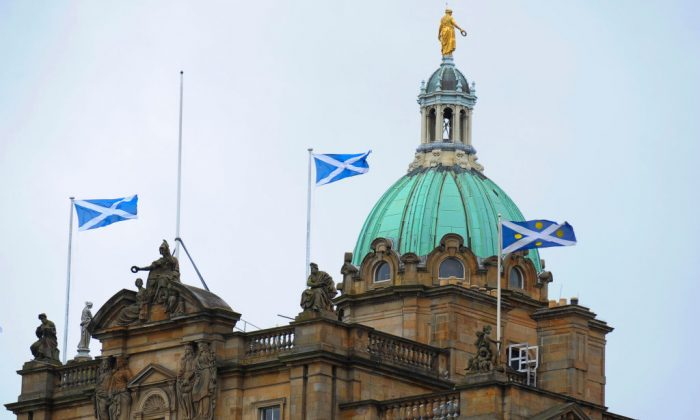 Saltire flags blow in the wind on top of The Bank of Scotland building on The Mound in Edinburgh on March 22, 2017. (Andy Buchanan/AFP/Getty Images)