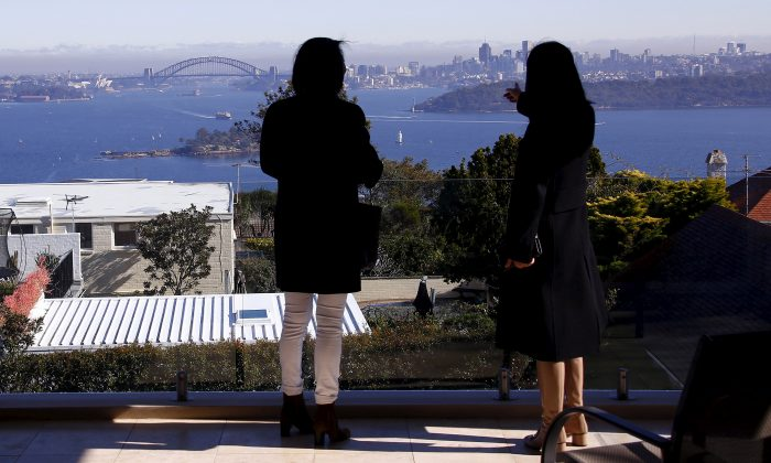 The Sydney Opera House and Harbour Bridge can be seen behind real estate agent and a potential buyer from Shanghai, during an inspection of a property for sale in the Sydney suburb of Vaucluse, Australia, July 11, 2015. (Reuters/David Gray/File Photo)