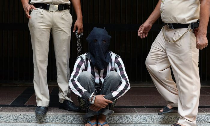 Indian police officers escort Ravinder Kumar, who is accused of murdering and sexual assaulting a 6-year-old girl, at a police station in New Delhi on July 20, 2015.  (Sajjad Hussain/AFP/Getty Images)