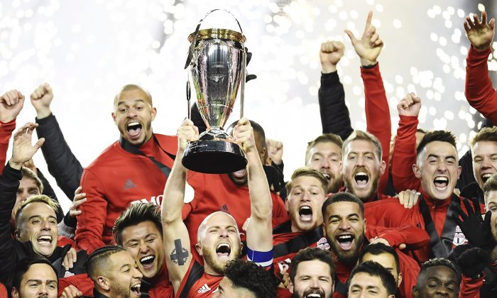 Toronto FC midfielder Michael Bradley raises the trophy as Toronto FC celebrate their victory over the Seattle Sounders in MLS Cup in Toronto on Dec. 9, 2017. (The Canadian Press/ Frank Gunn)