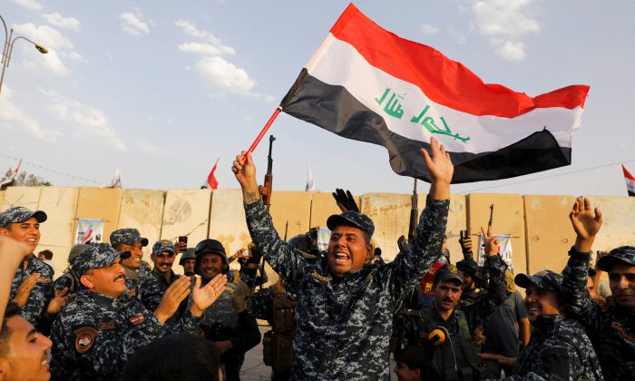 A member of Iraqi Federal Police waves an Iraqi flag as they celebrate victory of military operations against the Islamic State militants in West Mosul, Iraq July 2, 2017. (Reuters/Erik De Castro/File Photo)