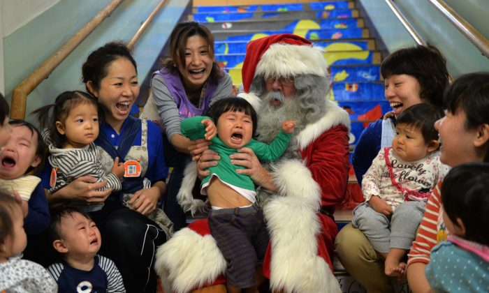A man playing Santa Claus (C) from Finland sits with children at the Hinomoto nursery school in Tokyo on December 9, 2013.  (Yoshikazu Tsuno/AFP/Getty Images)