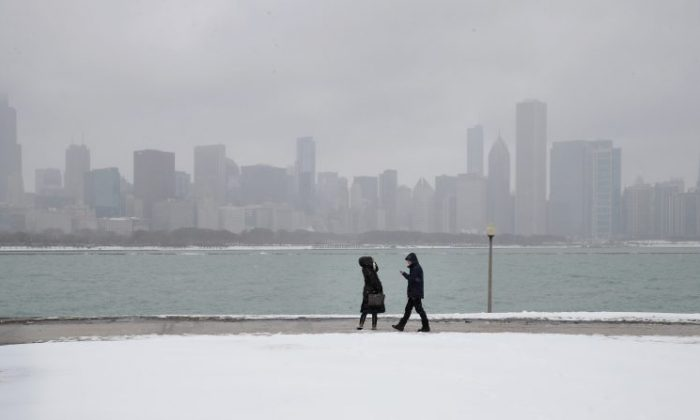 People walk along a snow-covered lakefront. (Scott Olson/Getty Images)