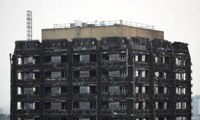 Workers stand on the roof of the burnt out remains of the Grenfell tower in London, Oct. 16, 2017. (Reuters/Hannah Mckay)