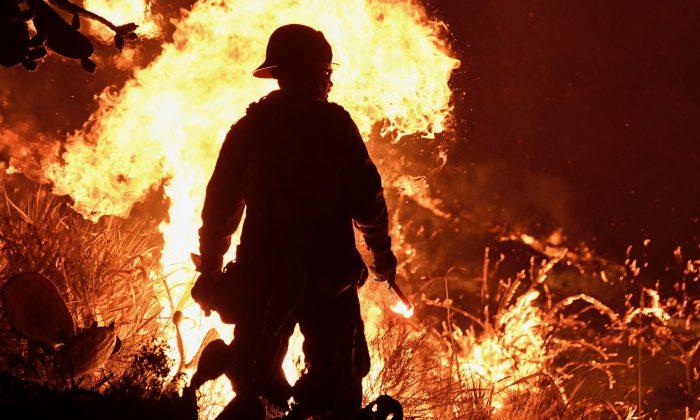 A firefighter battles a Santa Ana wind-driven brush fire called the Thomas Fire near Ventura. (Reuters/Gene Blevins)