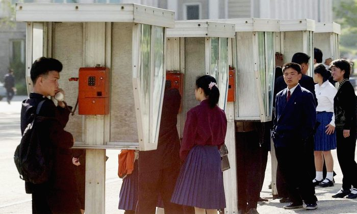 North Korean students use a public phone after school on May 6, 2004 in Pyongyang, North Korea. Landlines have been shut down in North Korea, possibly due to a leaked phone director. While cell phone usage is prevalent in the capital, landlines are used by budget conscious merchants and state-owned companies, many officials and businesses are struggling to communicate. (Pool/Getty Images)