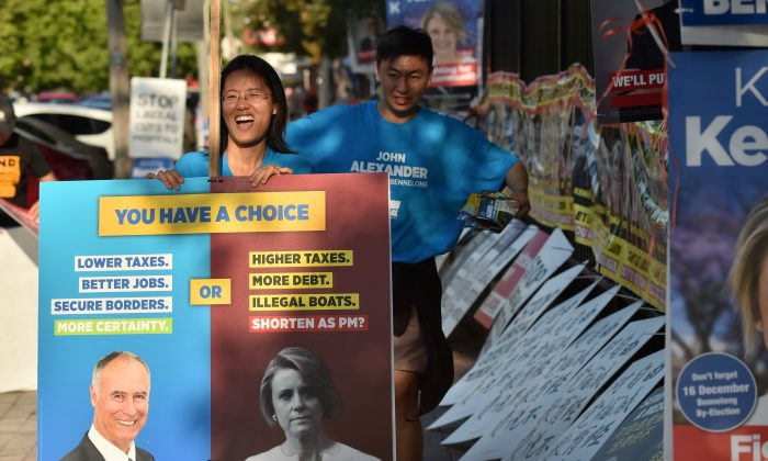Supporters of Liberal MP John Alexander pack away banners outside a polling station at the close of voting in the suburban Sydney seat of Bennelong on Dec. 16, 2017.  Alexander won back his seat in the Bennelong by-election after losing it due to his being a dual citizen. (Peter Parks/AFP/Getty Images)