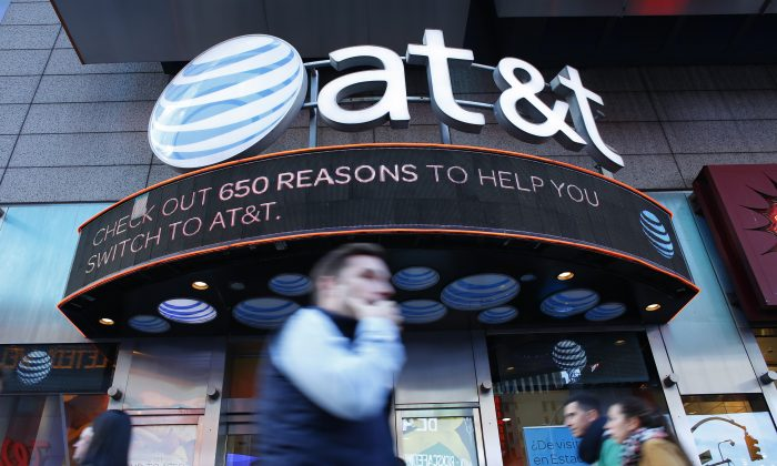People walk past an AT&T store in New York on Oct. 23, 2016. 