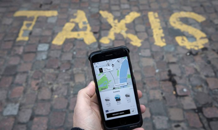 A photo illustration shows the Uber app on a mobile telephone, as it is held up for a posed photograph, in London, Nov. 10, 2017.  (Reuters/Simon Dawson/File Photo)