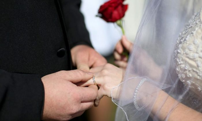 A couple exchanges rings as they are wed during a wedding. (Photo by Joe Raedle/Getty Images)