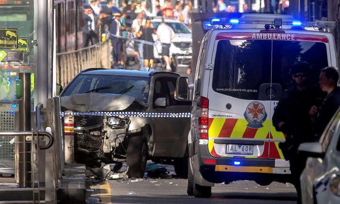 Australian police stand near a crashed vehicle after they arrested the driver of a vehicle that had ploughed into pedestrians at a crowded intersection near the Flinders Street train station in central Melbourne, Australia Dec. 21, 2017.  (Reuters/Luis Ascui)