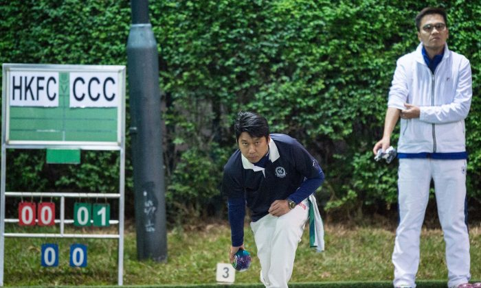 Lui Chin Hong (delivering) of Craigengower Cricket Club on his way to defeating Tony Cheung from the Hong Kong Football Club to lift the Men's Knockout Singles trophy on Sunday night (Dec 17). (Panda Man/ Takumi Photography)