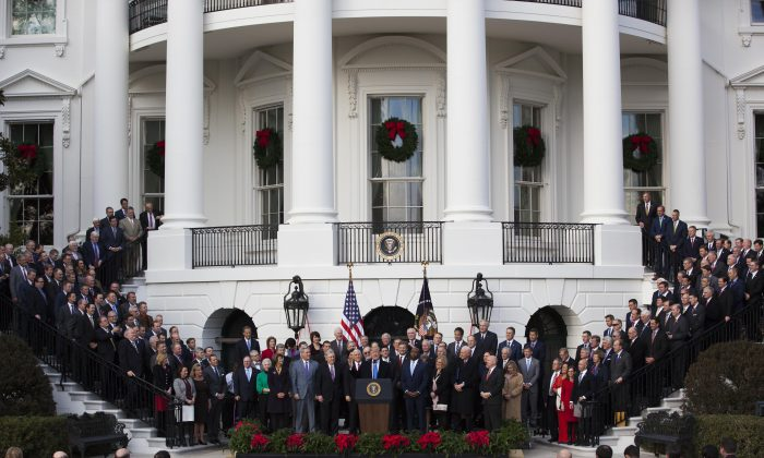 President Donald Trump celebrates the passage of the tax bill, while flanked by members of Congress, on the South Lawn of the White House in Washington, Dec. 20, 2017. (Charlotte Cuthbertson/The Epoch Times)
