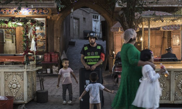 Uyghur children play while a local police officer looks on, in Kashgar, Xinjiang on June 29, 2017. Xinjiang is located in China's far northwest. (Kevin Frayer/Getty Images)