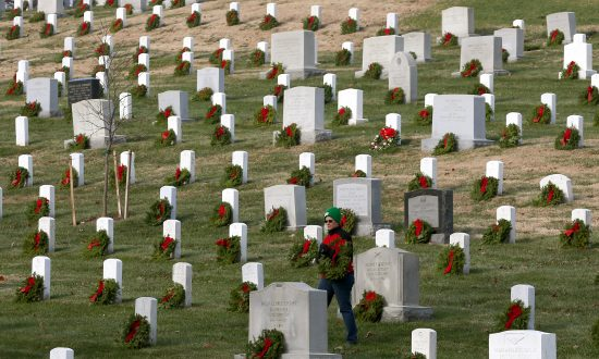 A volunteer looks for a grave to place a wreath on during the National Wreaths Across America Day at Arlington National Cemetery, in Arlington, Virginia in Dec. 13, 2014. (Mark Wilson/Getty Images)