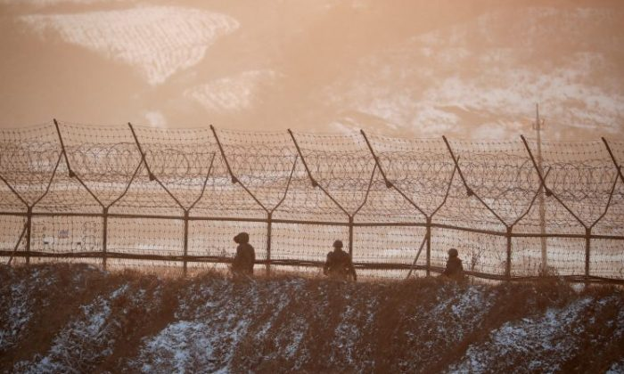 South Korean soldiers patrol along a barbed-wire fence near the militarized zone separating the two Koreas, in Paju, South Korea, on Dec. 21, 2017. (REUTERS/Kim Hong-Ji)