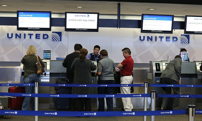 In this file image United Airlines passengers check in for flights at San Francisco International Airport. (Justin Sullivan/Getty Images)