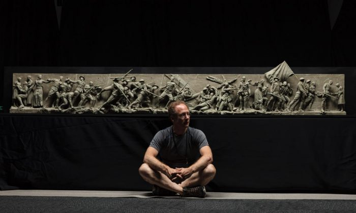 "Sculptor Sabin Howard sits with the maquette he created for ""A Soldier's Journey,"" the sculptural component of the National World War I Memorial, at Weta Workshop in Wellington, New Zealand, in November 2017. (Courtesy of Sabin Howard)"