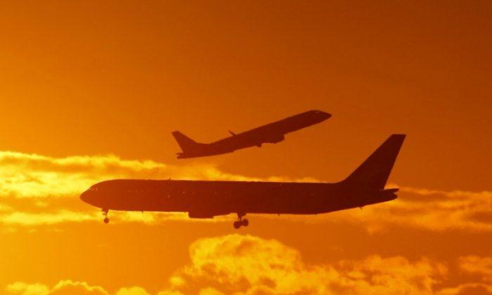 Passenger planes land and take off at Sydney airport April 28, 2009. (Reuters/Tim Wimborne)