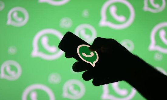 A man poses with a smartphone in front of displayed Whatsapp logo in this illustration Sept. 14, 2017. (Reuters/Dado Ruvic)