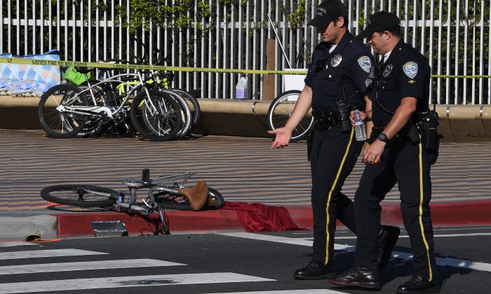 Police walk past a damaged bike at the scene of a six car accident after an elderly woman driver severely injured a cyclist and collided with the other vehicles at the entrance to the historic Santa Monica Pier in Santa Monica, Calif. on April 19, 2017. (Mark Ralston/AFP/Getty Images)